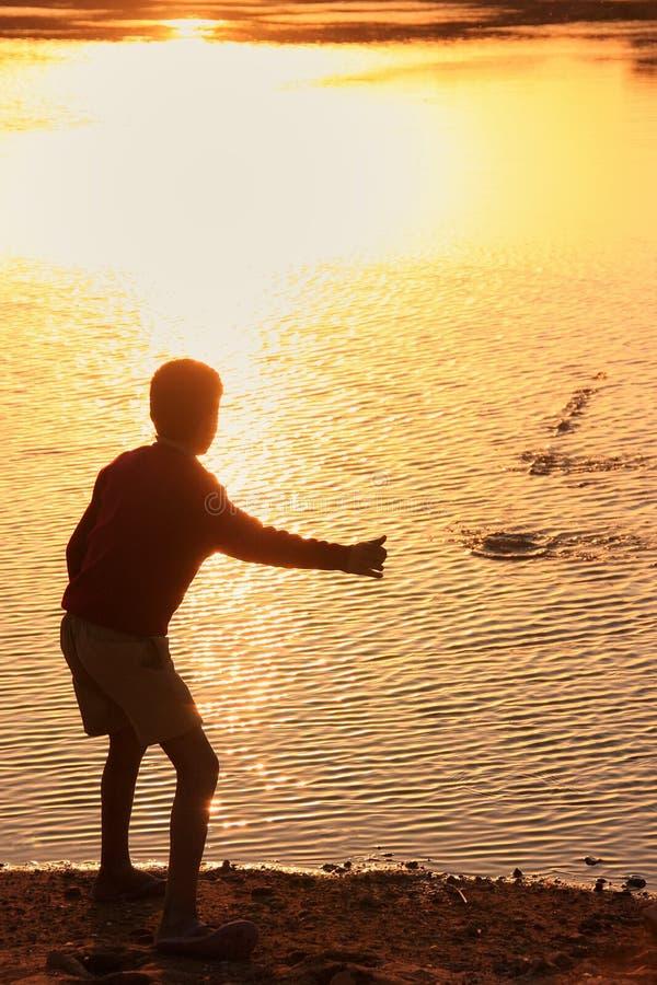 Силуэт камней мальчика бросая в воде, деревня Khichan, стоковое изображение