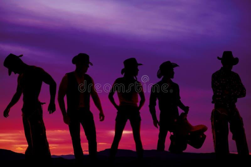 Силуэт ковбоев в заходе солнца стоковое фото rf