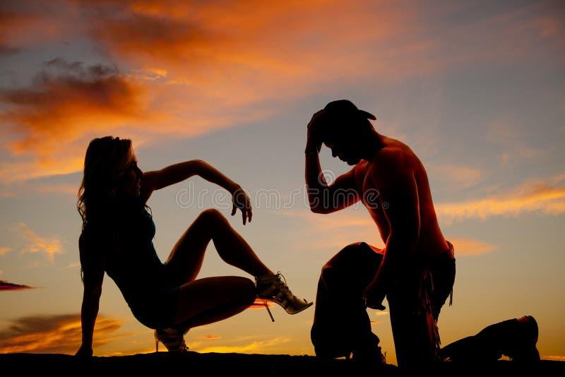 Силуэт ковбоя на колене и женщина сидят назад одна нога вверх в th стоковая фотография