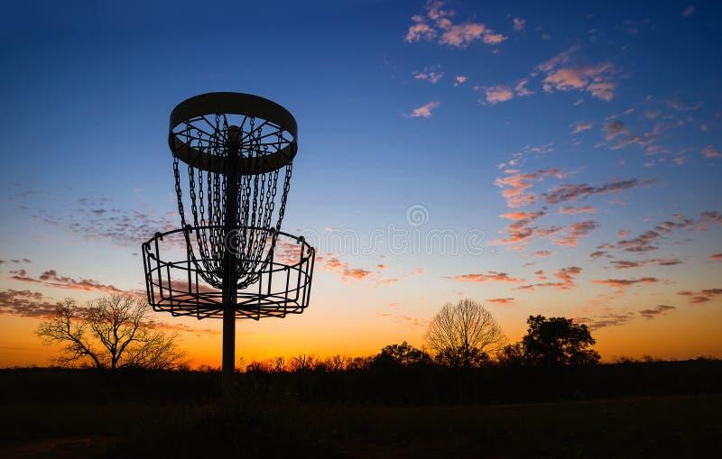 Силуэт корзины гольфа диска против захода солнца стоковые изображения