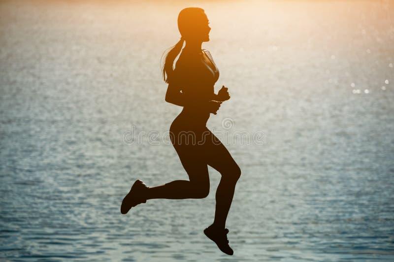 Силуэт красивой, атлетической женщины скача во время спорт около реки на заходе солнца стоковые фотографии rf