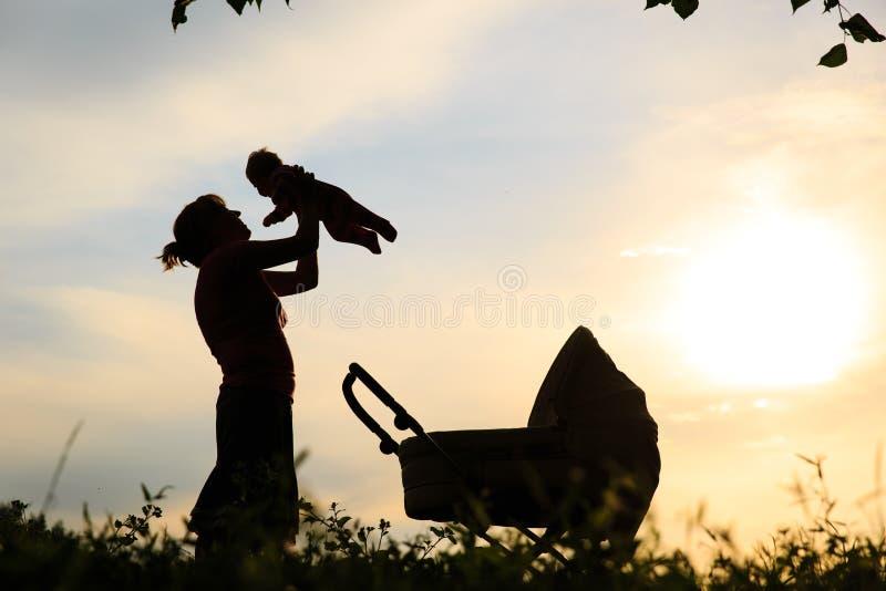 Силуэт матери с маленькими младенцем и прогулочной коляской на небе стоковое изображение