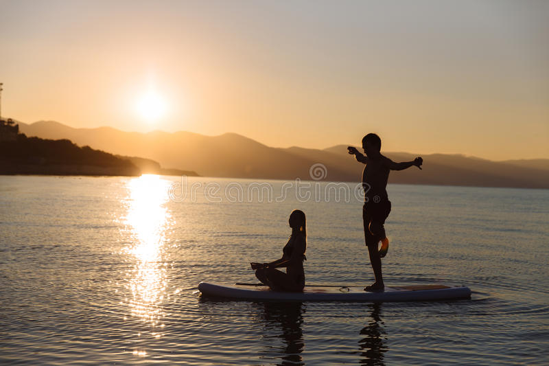 Силуэт мальчика в представлении йоги и девушка сидя на маленьком глотке занимаются серфингом на океане Образ жизни концепции, спо стоковые фотографии rf