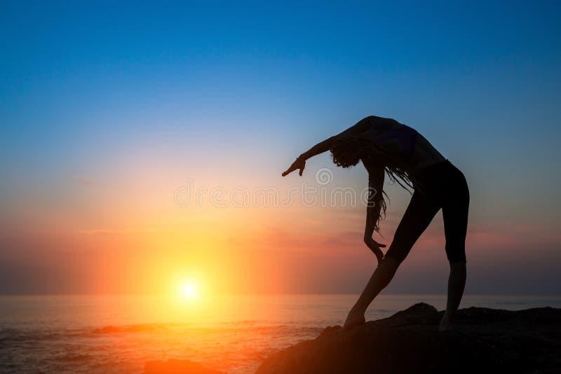 Силуэт молодой женщины выполняя фитнес работает на морском побережье стоковые изображения