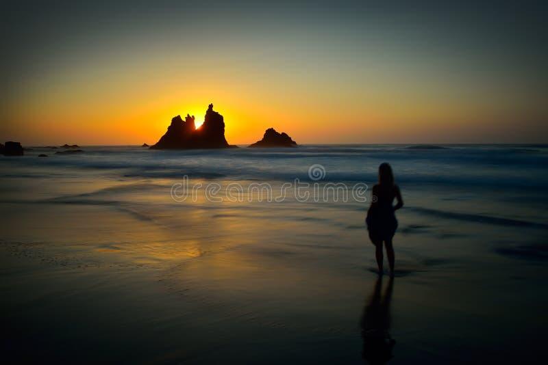 Силуэт молодой женщины на пляже на заходе солнца стоковая фотография