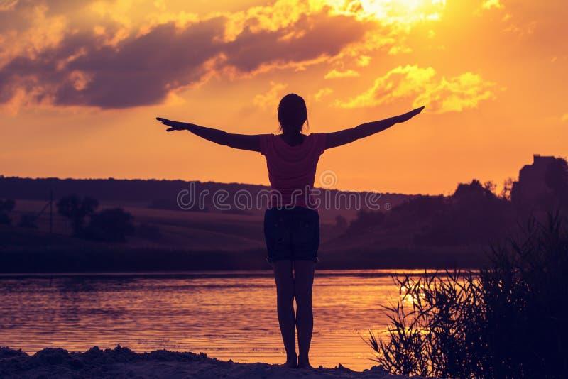Силуэт молодой женщины с оружиями поднял в фоне заходящего солнца стоковое изображение