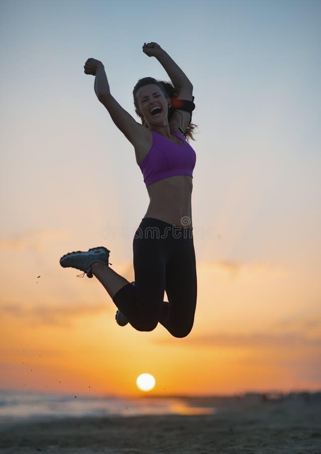 Силуэт молодой женщины фитнеса скача на пляж на сумраке стоковое изображение