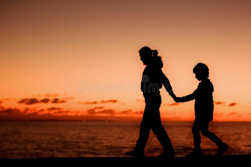 Силуэт молодой матери и ее идти сына стоковые фотографии rf