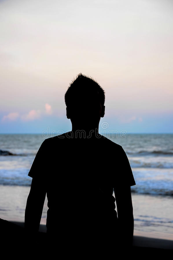 Силуэт молодых парней играя на пляже во время захода солнца стоковые фотографии rf