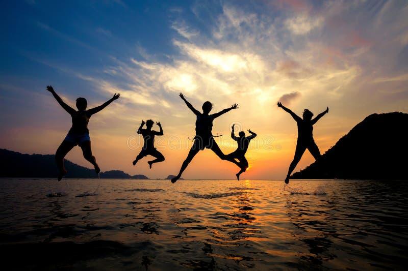 Силуэт молодых друзей имея потеху на пляже и скакать стоковая фотография rf