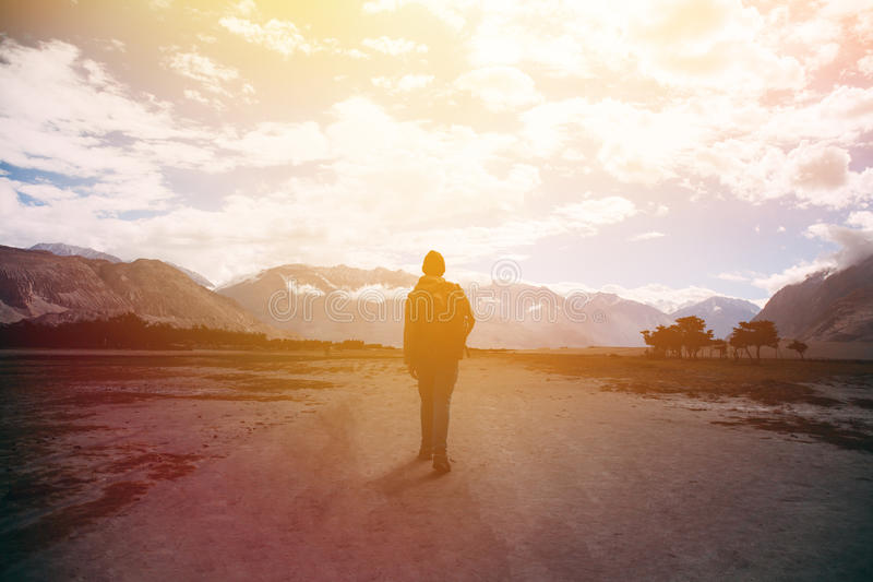 Силуэт мужского путешественника с рюкзаком идя против солнечного света в зоне гористой местности горы стоковая фотография rf