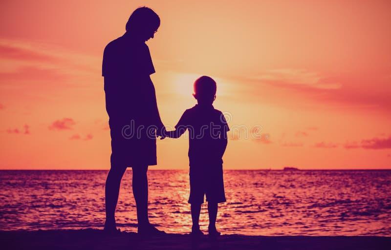 Силуэт отца и сына держа руки на море захода солнца стоковые изображения rf