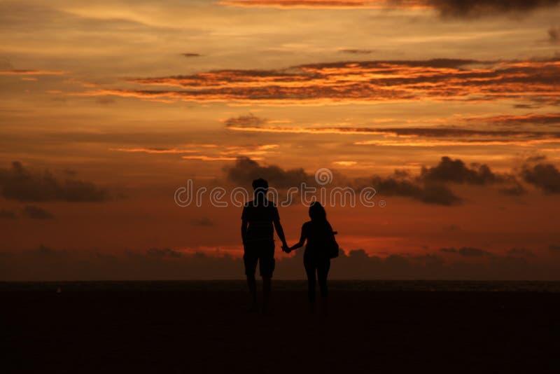 Силуэт пары держа руки на пляже на сумраке стоковое фото