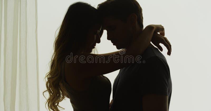 Силуэт пар быть интимный перед окном стоковая фотография rf