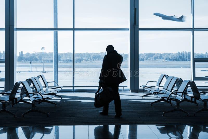 Силуэт пассажира ждать полет в авиапорт стоковые фото