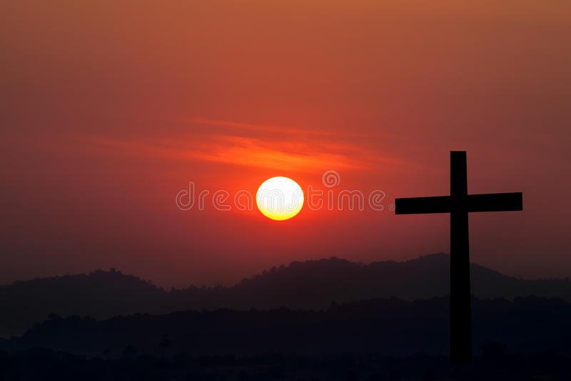 Силуэт пересекает сверх предпосылку захода солнца стоковое фото rf