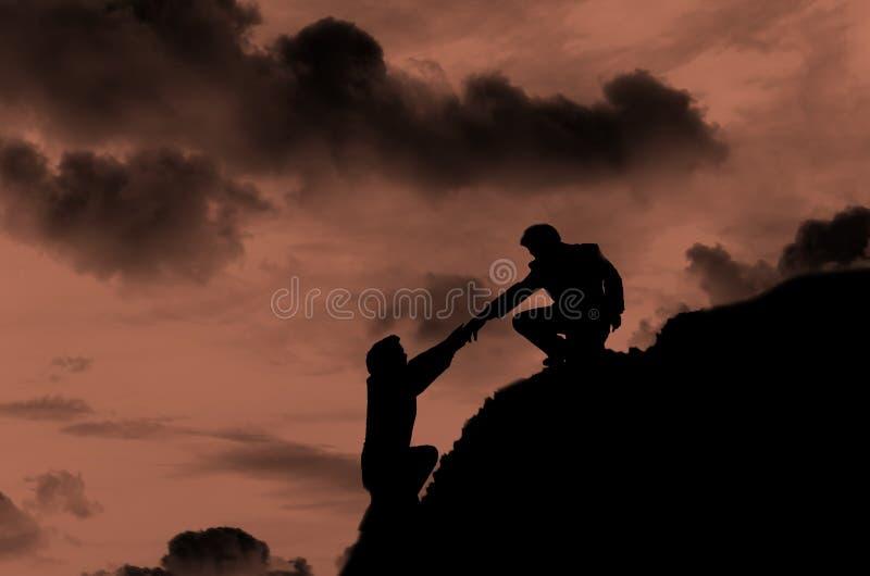 Силуэт персоны людей помогая на горе стоковое фото rf