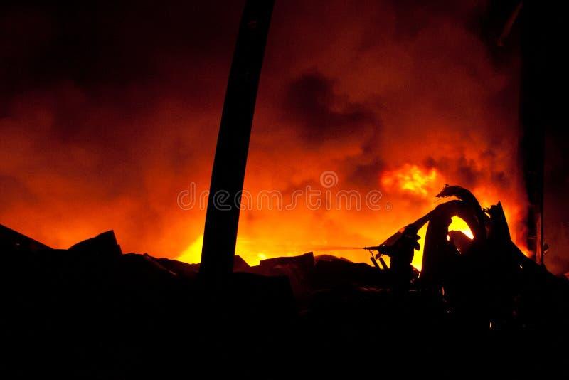 Силуэт пожарных воюя бушующий пожар с огромными пламенами стоковое фото rf