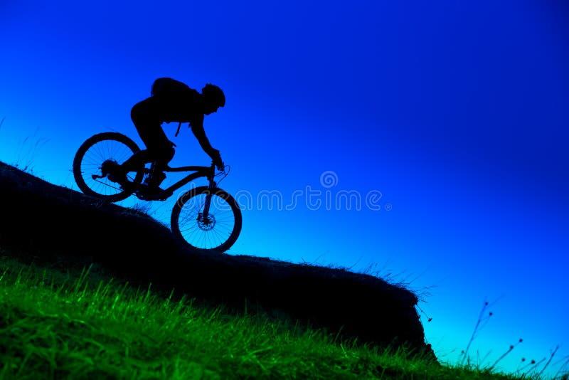 Силуэт покатого всадника горного велосипеда стоковая фотография rf