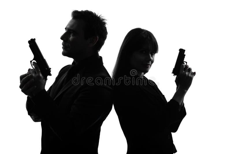 Силуэт преступника тайного агента человека женщины пар сыщицкий стоковое изображение