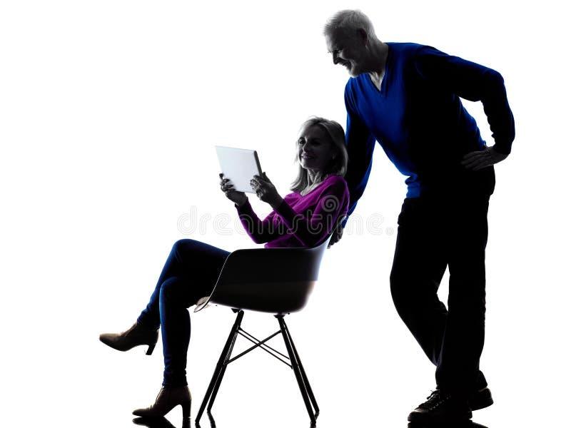 Силуэт планшета пар старший цифровой стоковая фотография