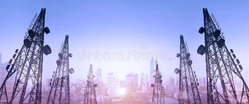 Силуэт, радиосвязь возвышается с антеннами ТВ и спутниковой антенна-тарелкой в заходе солнца, с городом двойной экспозиции в back стоковые фото