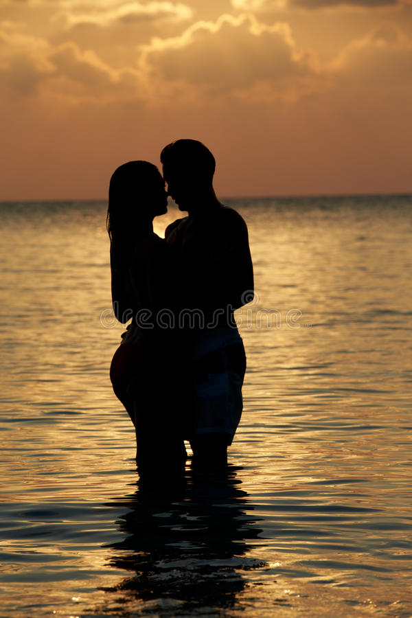 Силуэт романтичных пар стоя в море стоковая фотография rf