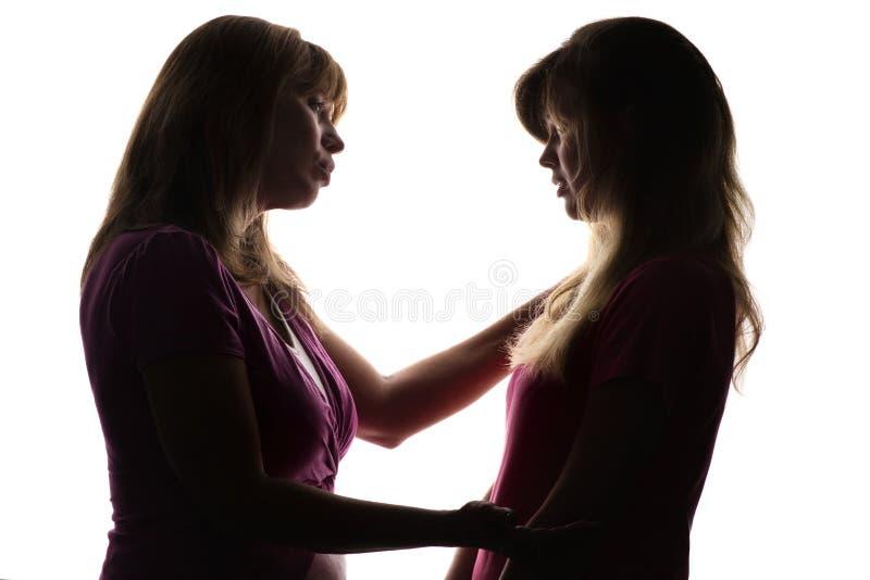 Силуэт дружелюбных отношений между матерью и подростком дочери, матерью дает совет с влюбленностью стоковое изображение rf