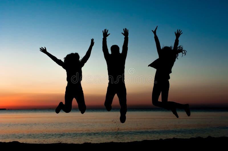 Силуэт друзей скача на пляж стоковые фотографии rf