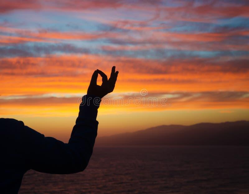 Силуэт руки в mudra на заходе солнца стоковая фотография