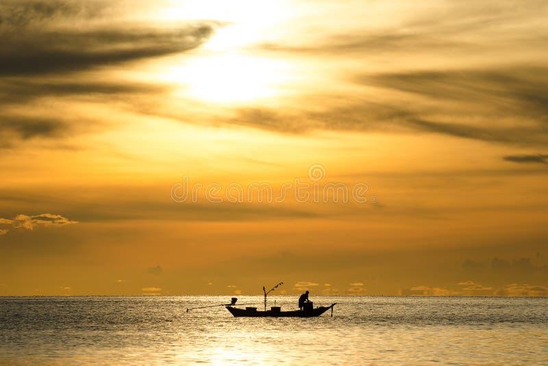 Силуэт рыболовов в шлюпке на море с желтым и оранжевым солнцем на заднем плане стоковое фото