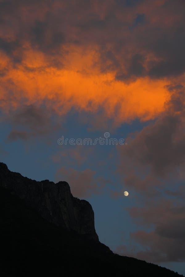 Силуэт саммита красивых горы Gemu святых и луны в пламенеющем зареве вечера, Юньнань, Китая стоковые изображения