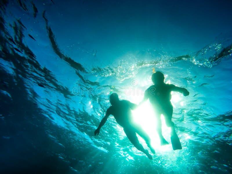 Силуэт старших пар плавая совместно в тропическом море стоковые фотографии rf