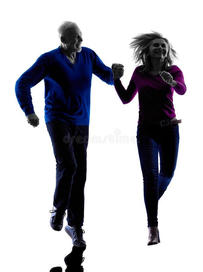 Силуэт старшия пар бежать скача счастливый стоковое изображение