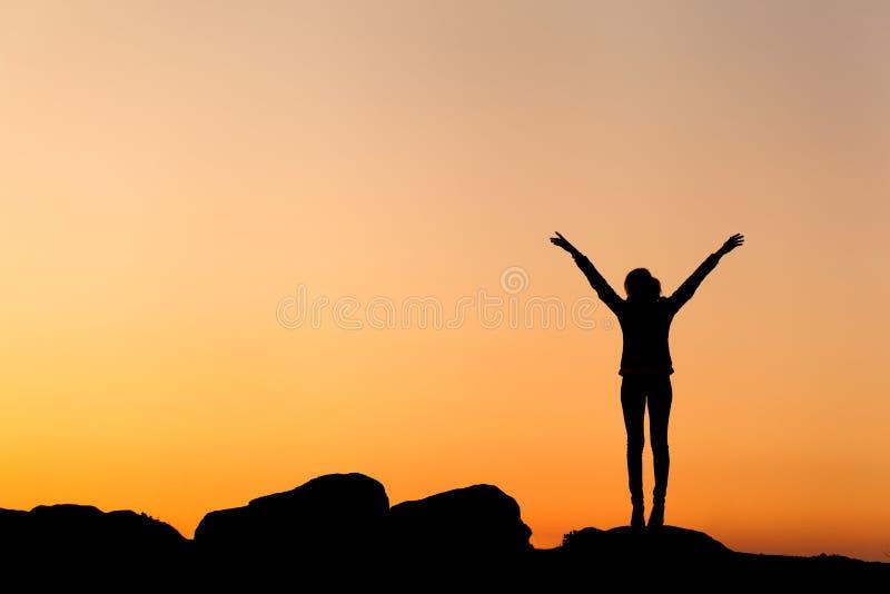 Силуэт счастливой молодой женщины против красивого красочного неба стоковые фотографии rf