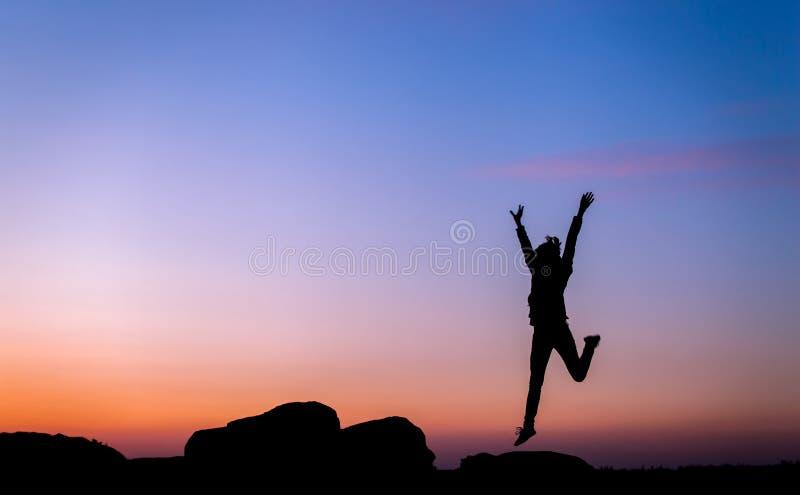 Силуэт счастливой молодой женщины против красивого красочного неба стоковые изображения