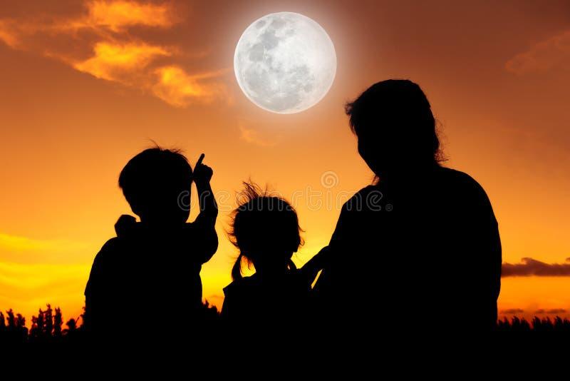 Силуэт счастливой семьи сидя и смотря небо на заходе солнца стоковое фото rf