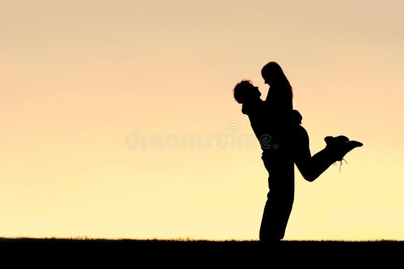 Силуэт счастливых молодых пар обнимая снаружи на заходе солнца стоковые фото