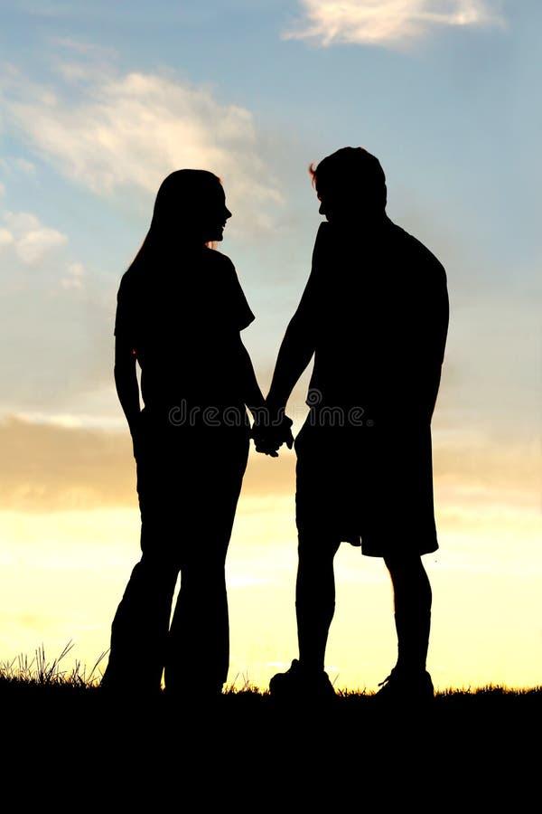 Силуэт счастливых пар держа руки и говоря на заходе солнца стоковые фото