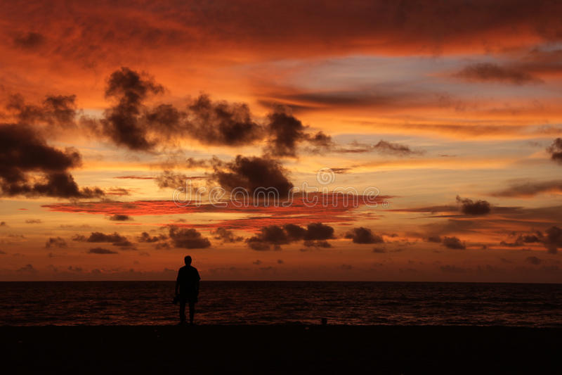 Силуэт уединённого человека на пляже на сумраке стоковое изображение