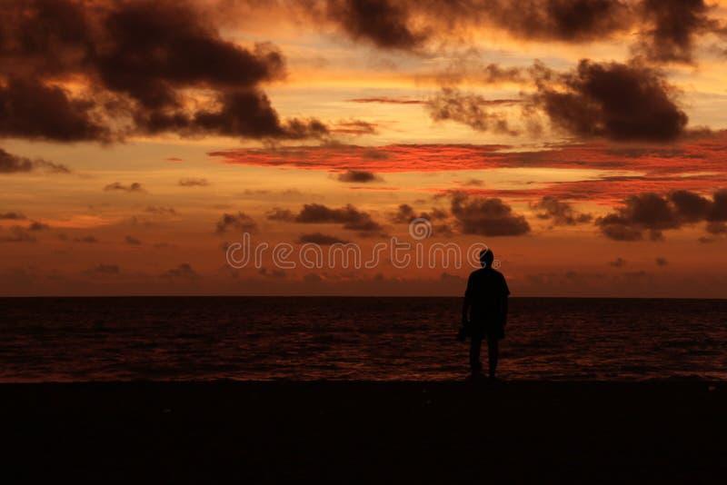 Силуэт уединённого человека на пляже на сумраке стоковые фото