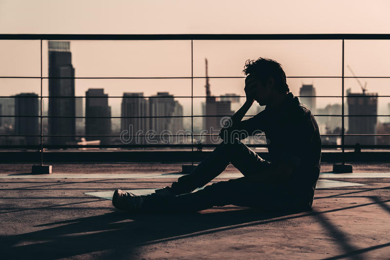 Силуэт унылым подавленным азиатским надежды и выкрика потерянных человеком, сидит на крыше здания на заходе солнца, темном тоне н стоковое изображение