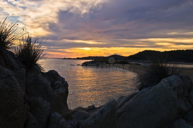 Силуэт утесов моря и отражение cloudscape на заходе солнца стоковое фото rf