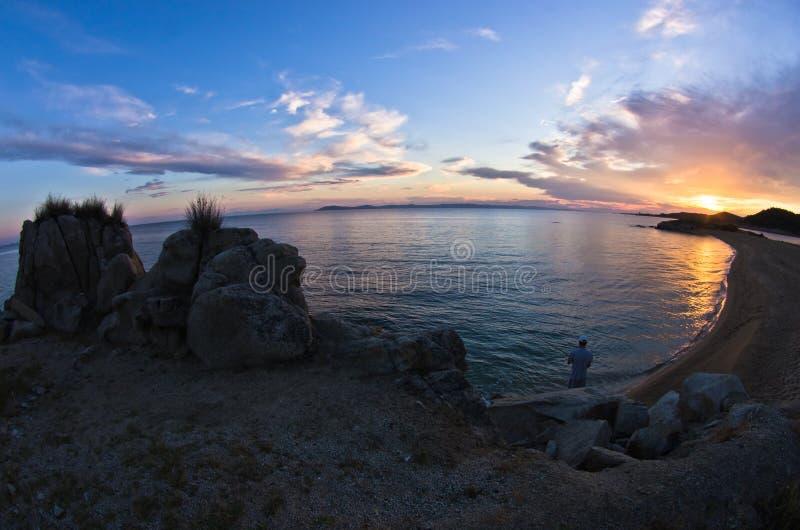 Силуэт утесов моря и отражение cloudscape на заходе солнца стоковая фотография rf