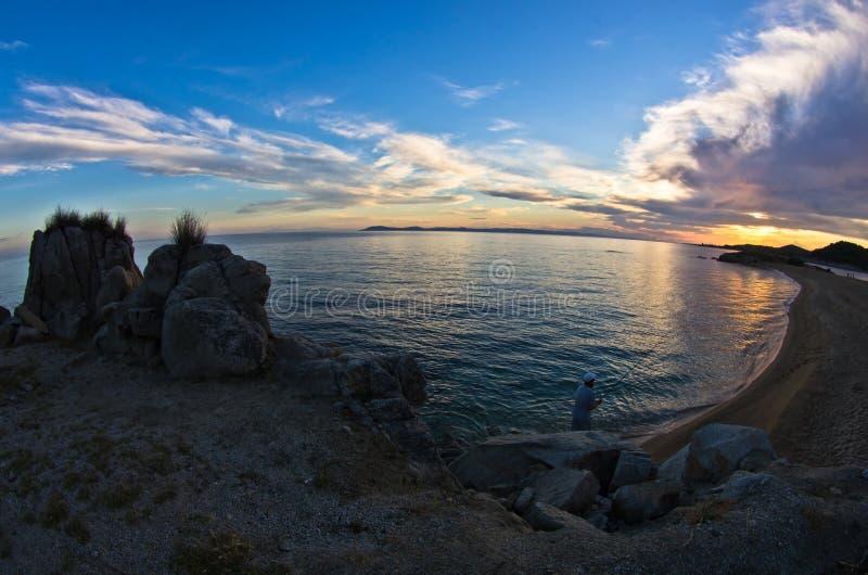 Силуэт утесов моря и отражение cloudscape на заходе солнца стоковые изображения
