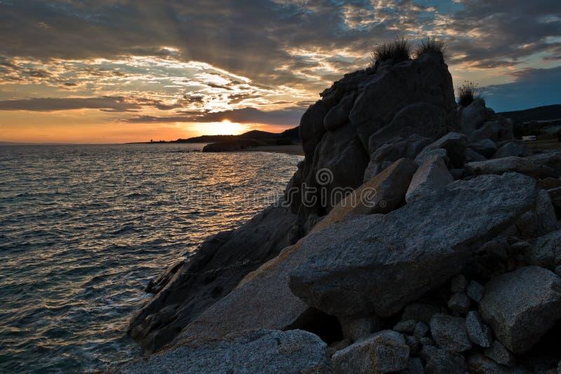 Силуэт утесов моря и отражение cloudscape на заходе солнца стоковое фото
