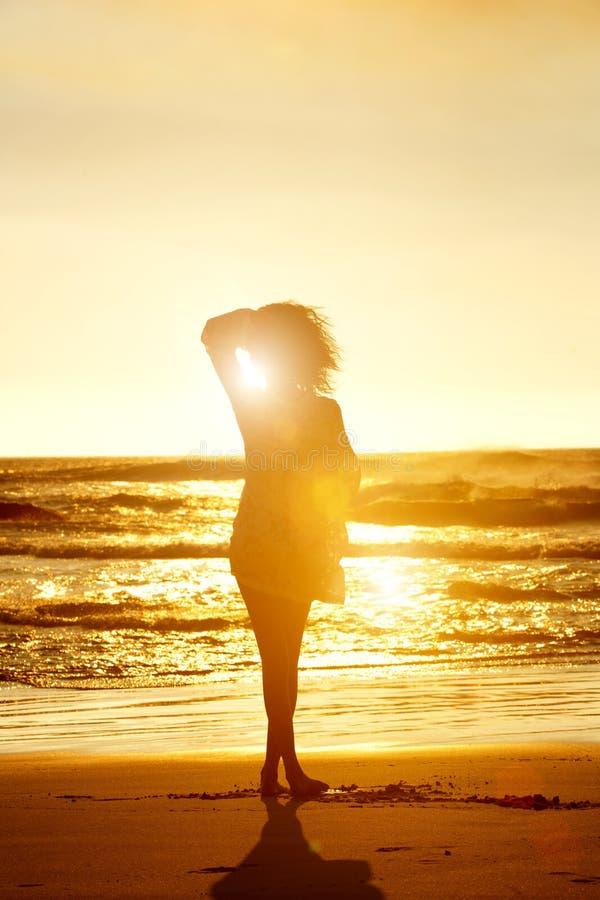 Силуэт фотомодели идя на пляж во время захода солнца стоковая фотография rf