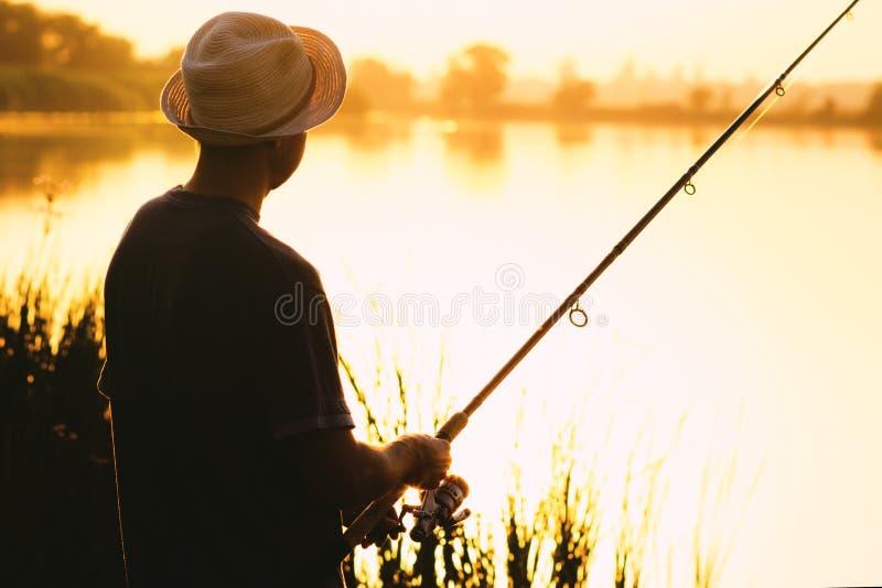 Силуэт человека в шляпе приниматься рыбную ловлю спорта Стоковое ...