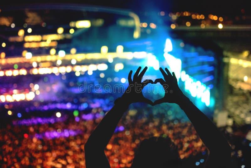 Силуэт человека делая сердце от жестов рукой, винтажный взгляд на фото и предпосылку толпы стоковые изображения rf