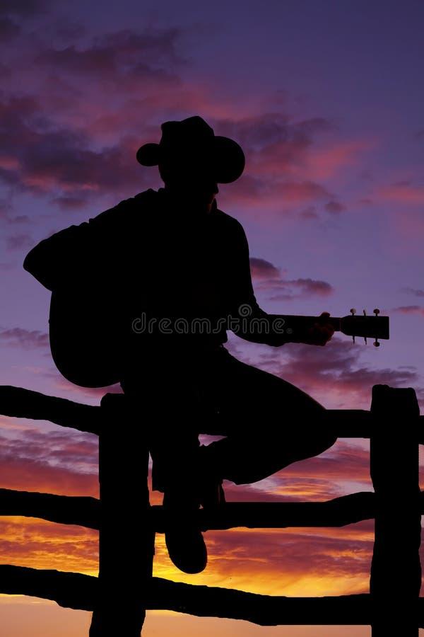 Силуэт человека на загородке с гитарой стоковые фото